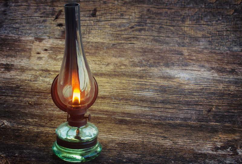 木桌上燃烧的煤油灯