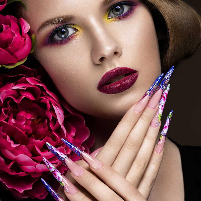 花为背景有着夸张指甲的彩妆女人