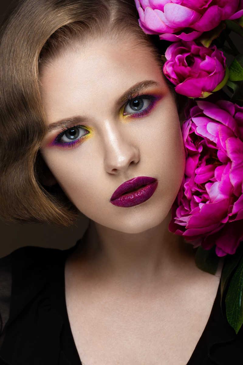 花为背景的年轻的彩妆女性