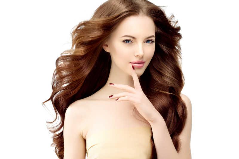 拥有一头漂亮的棕色卷发的美丽女郎