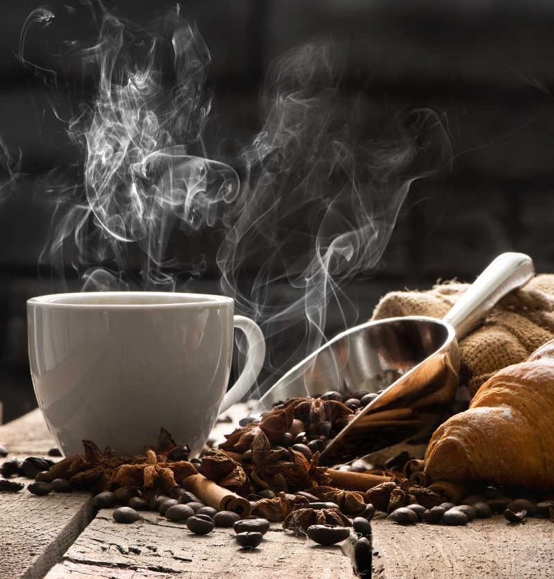 旧木桌上的热咖啡和牛角包