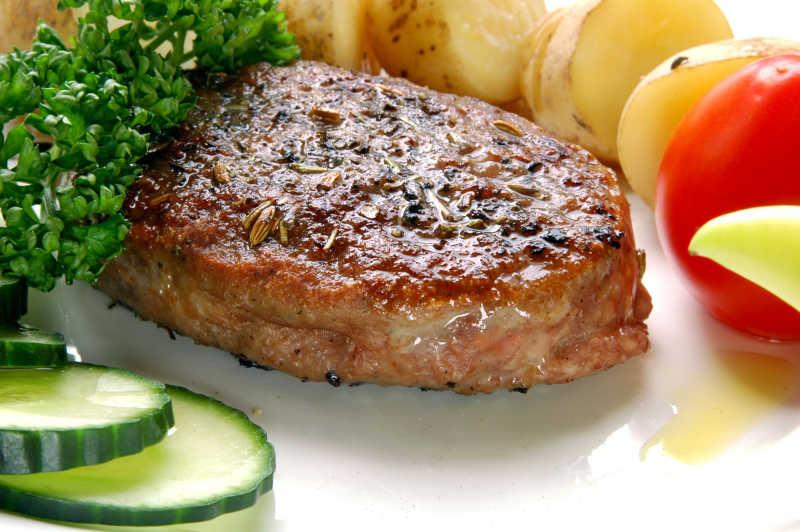 白色背景下的烤肉片和蔬菜