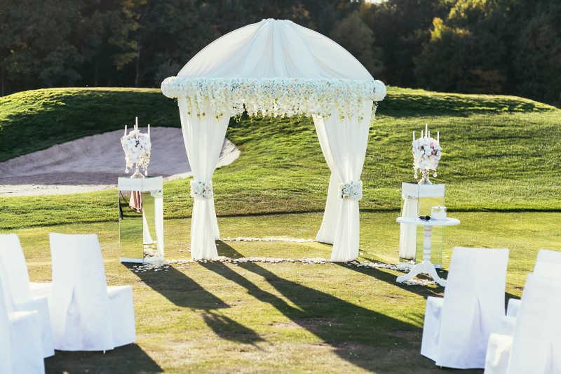 鲜花和白色幔布装饰的婚礼现场