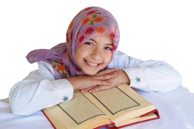 白色背景下读古兰经的穆斯林小美女