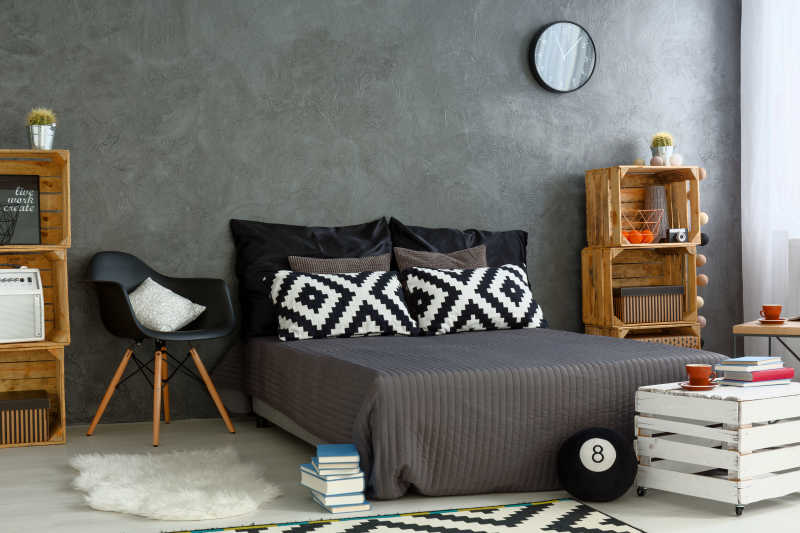 卧室中摆放着灰色的床和书架