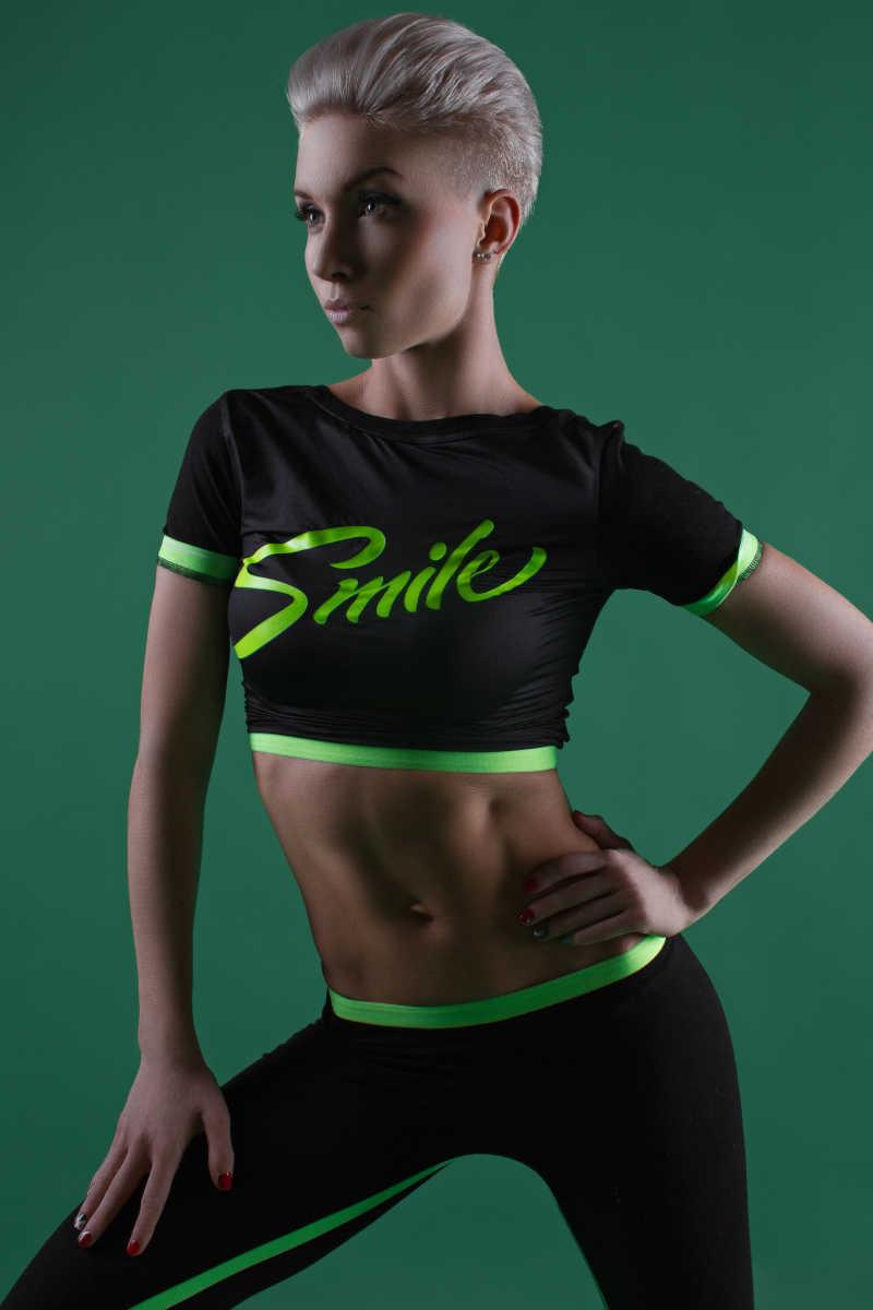 绿色背景前健身的女人