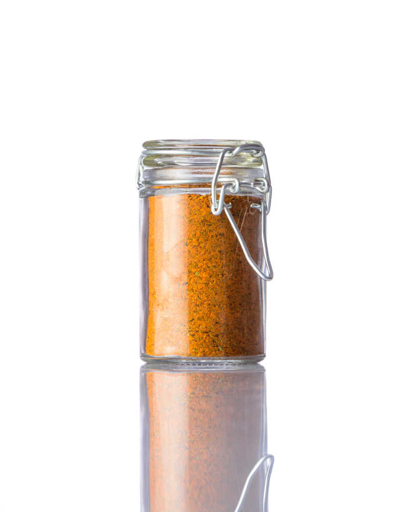 白色背景下咖喱粉的玻璃罐子
