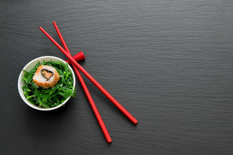 红色筷子旁碗里的寿司和海草卷