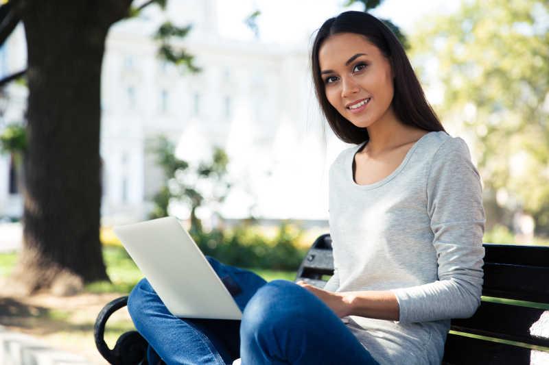 在公园的木椅上使用笔记本电脑的微笑的女孩