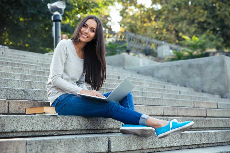 美丽的长发女孩坐在台阶上使用笔记本电脑