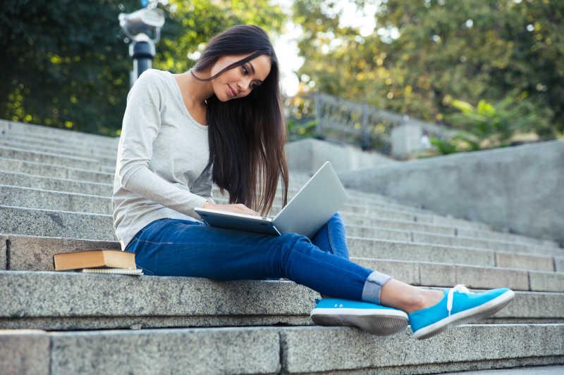 坐在台阶上低头使用笔记本电脑的青春靓丽的女孩