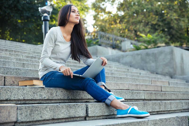 坐在户外台阶上拿着笔记本电脑看着远处的女孩
