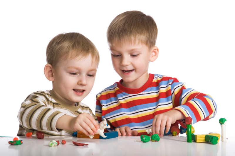 白色背景上在桌上玩橡皮泥的两个金发男孩
