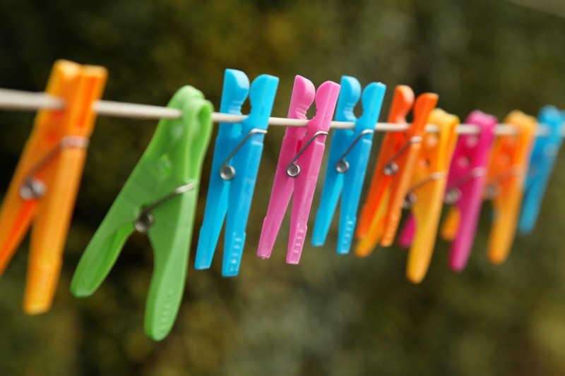 户外绿色背景下夹满彩色夹子的晾衣绳