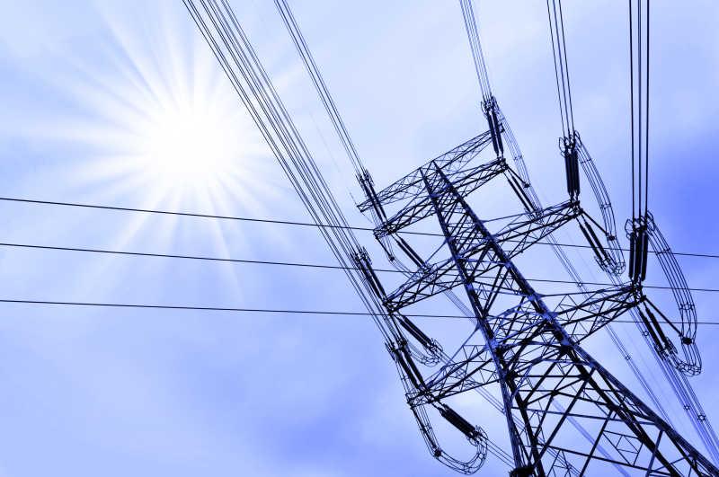 晴天阳光下的高压电力塔架和线路电缆