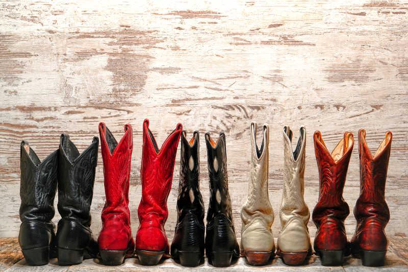 木制背景下排列整齐的几双靴子
