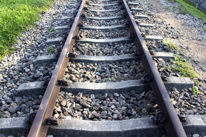 绿色草地旁边的旧的铁路钢轨