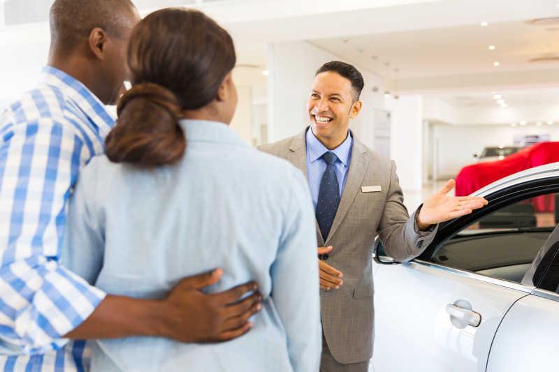 汽车经销商微笑着给客户介绍