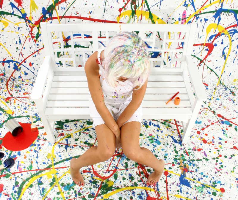 坐在涂满颜料屋里的白色凳子上的女孩