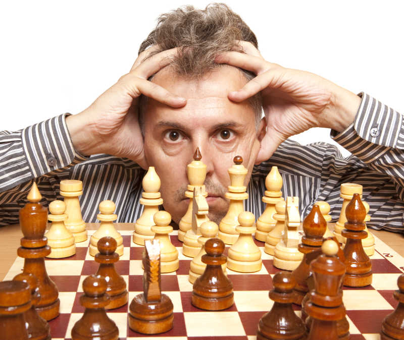 男子双手抱头盯着棋盘上的棋子