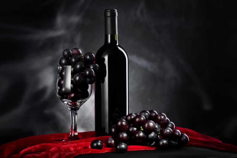 黑色背景上的葡萄与葡萄酒