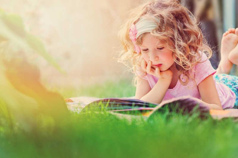 小女孩趴在草地上看书
