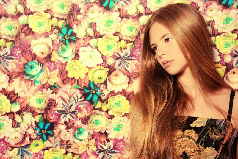 漂亮的花墙前的穿夏装的长发女孩