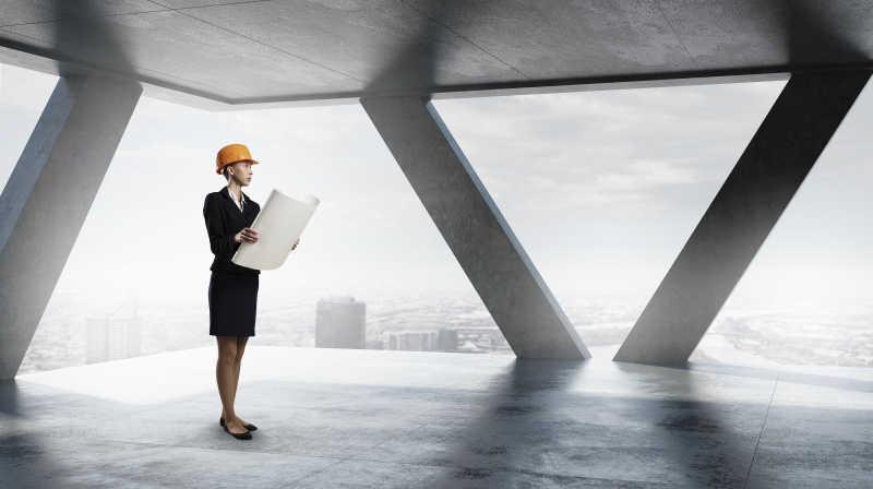 带安全帽的年轻女工程师在室内