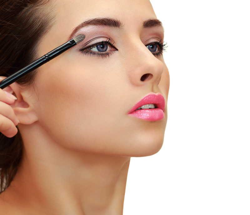 漂亮的女人用眼影刷画眼影