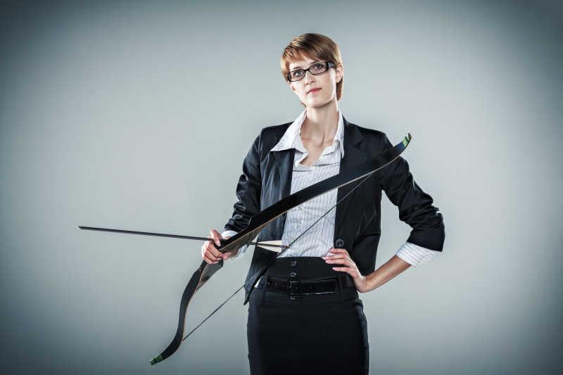 灰色背景下拿着弓箭的女
