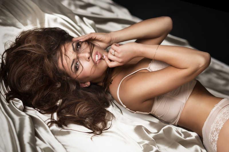 迷人的性感黑发女人躺在床上