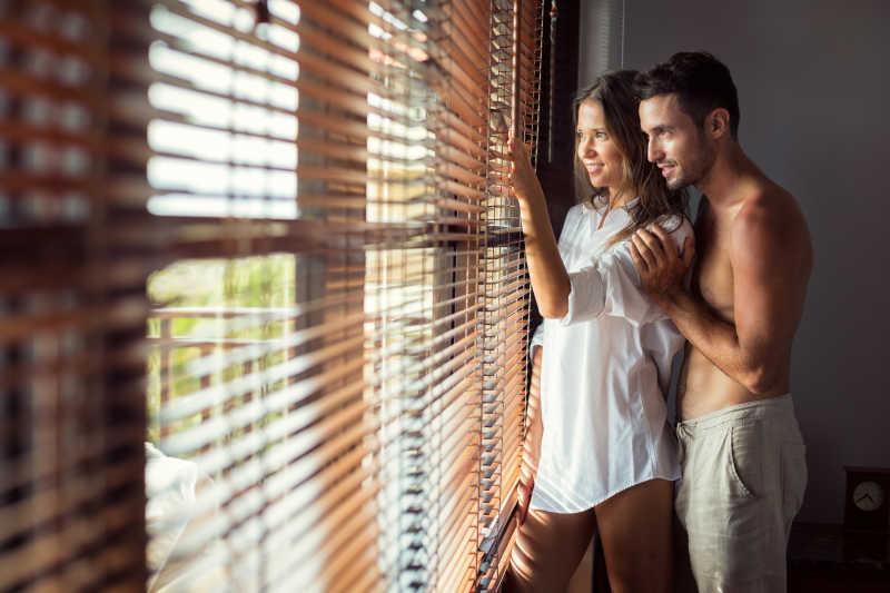 海边度假别墅的窗户边有一对情侣