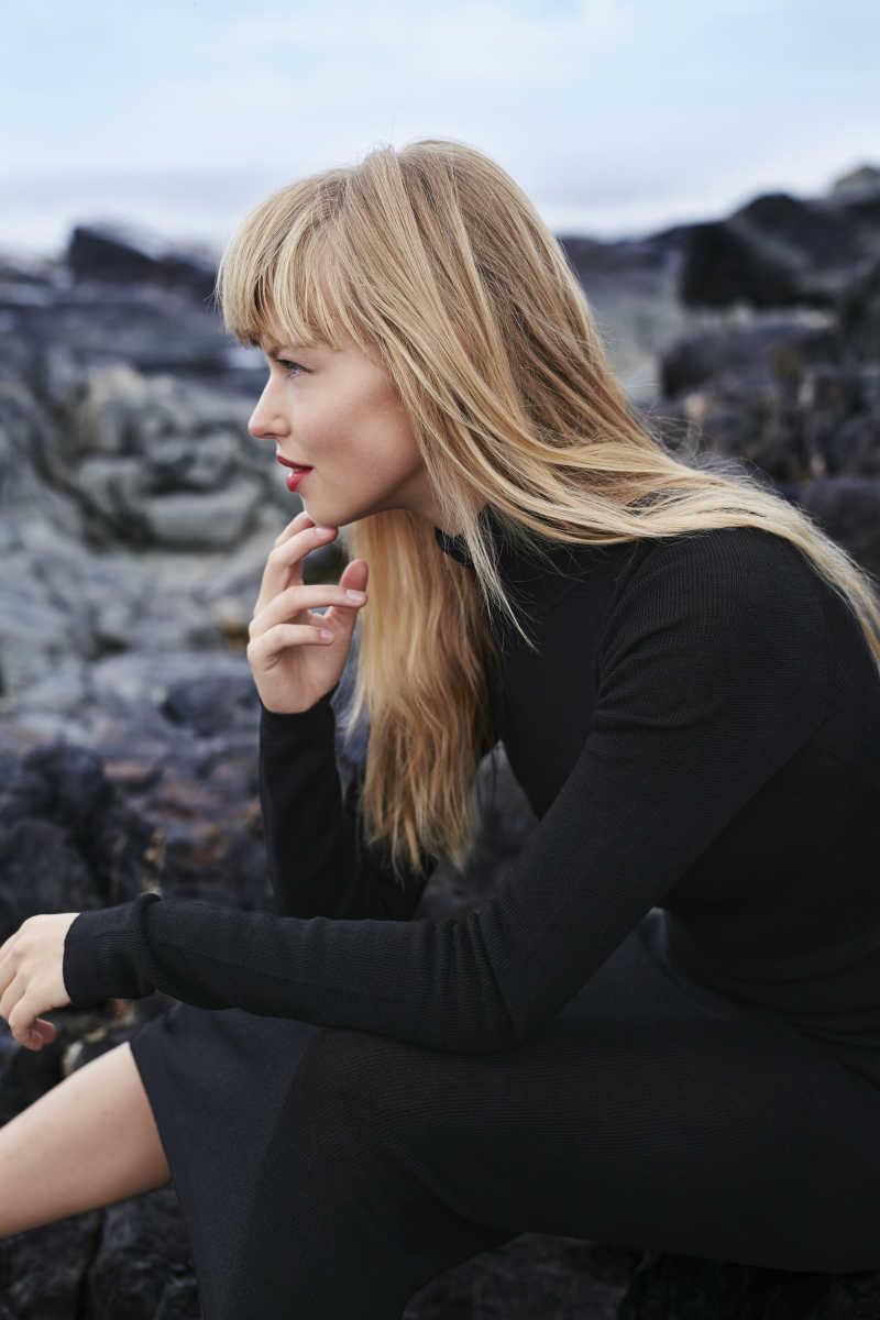 在岩石上沉思的金发美女