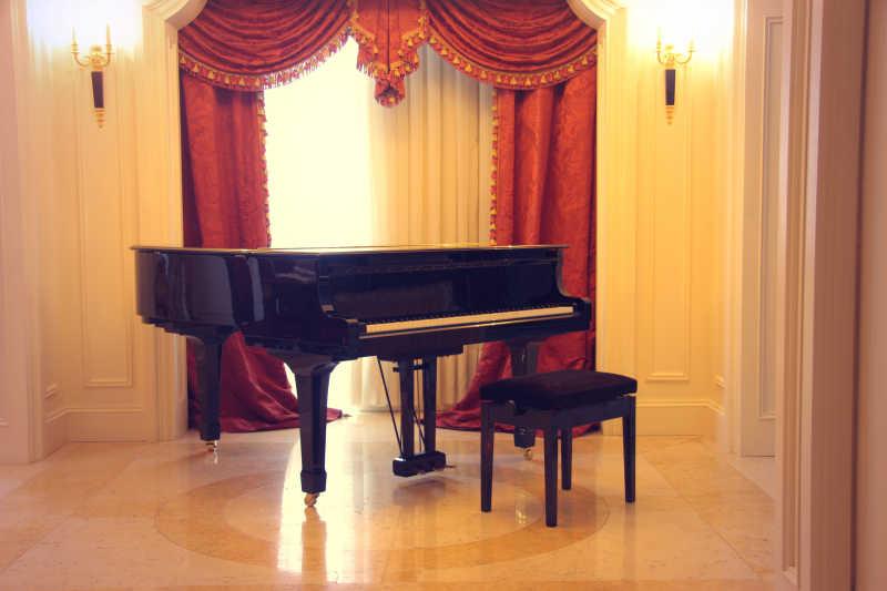 红色窗帘边精力的黑色钢琴