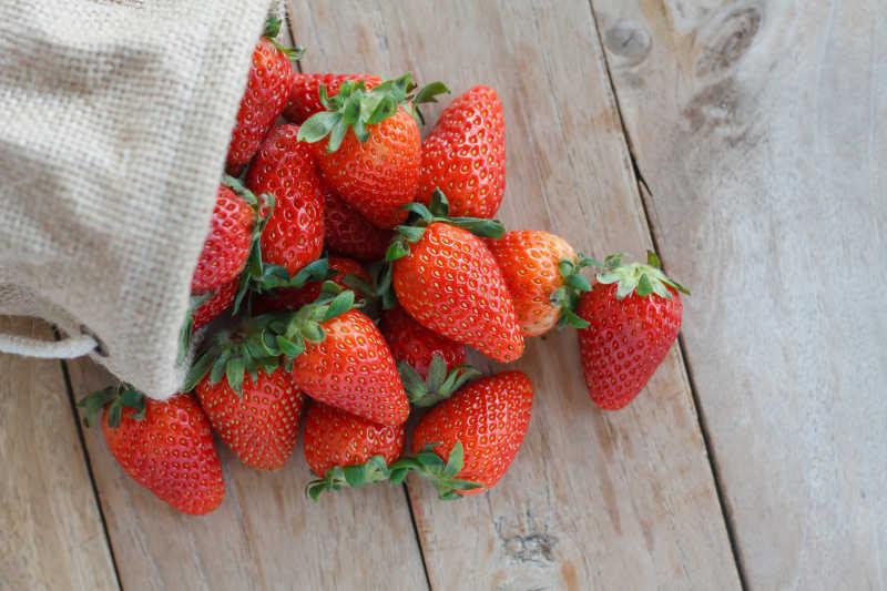 木桌上小袋子里的草莓