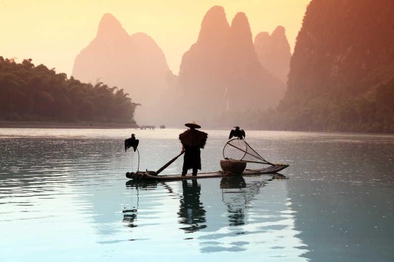 乘坐木筏用鸬鹚捕鱼的渔翁