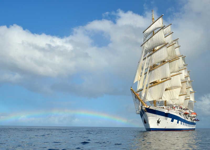 彩虹背景下的白色帆船
