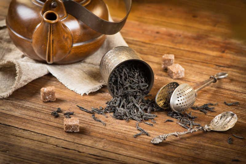木桌上倒出来的茶叶和茶具