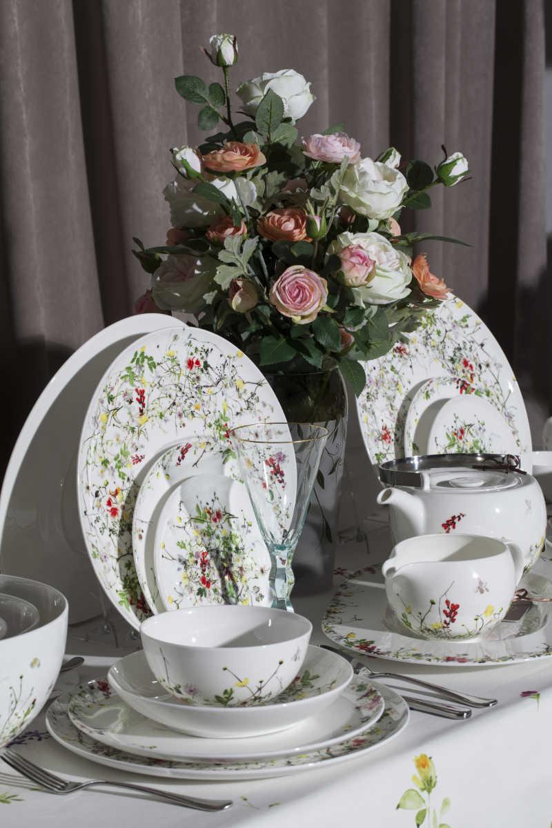餐具边摆放的美丽的鲜花
