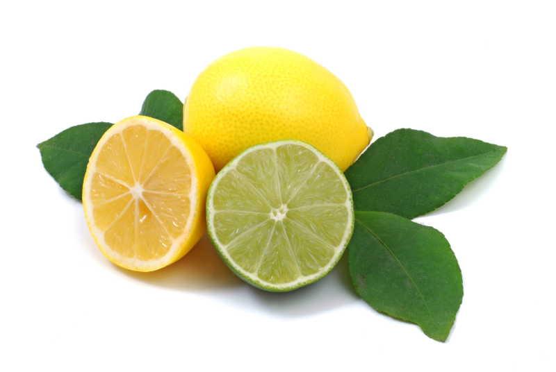 白色背景上新鲜的切开的带绿叶柠檬