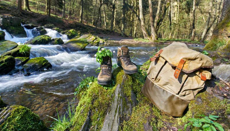 小溪边的登山鞋与旅行包