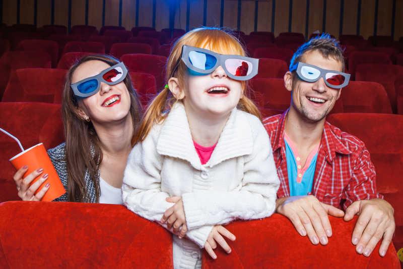 坐在电影院里看电影的快乐家庭
