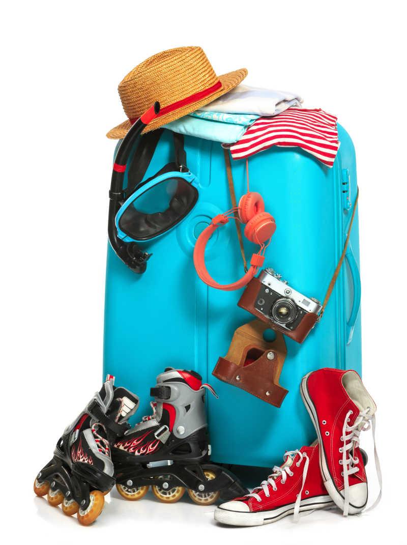 白色背景下放着运动鞋帽子照相机等外出旅行物品的旅行箱