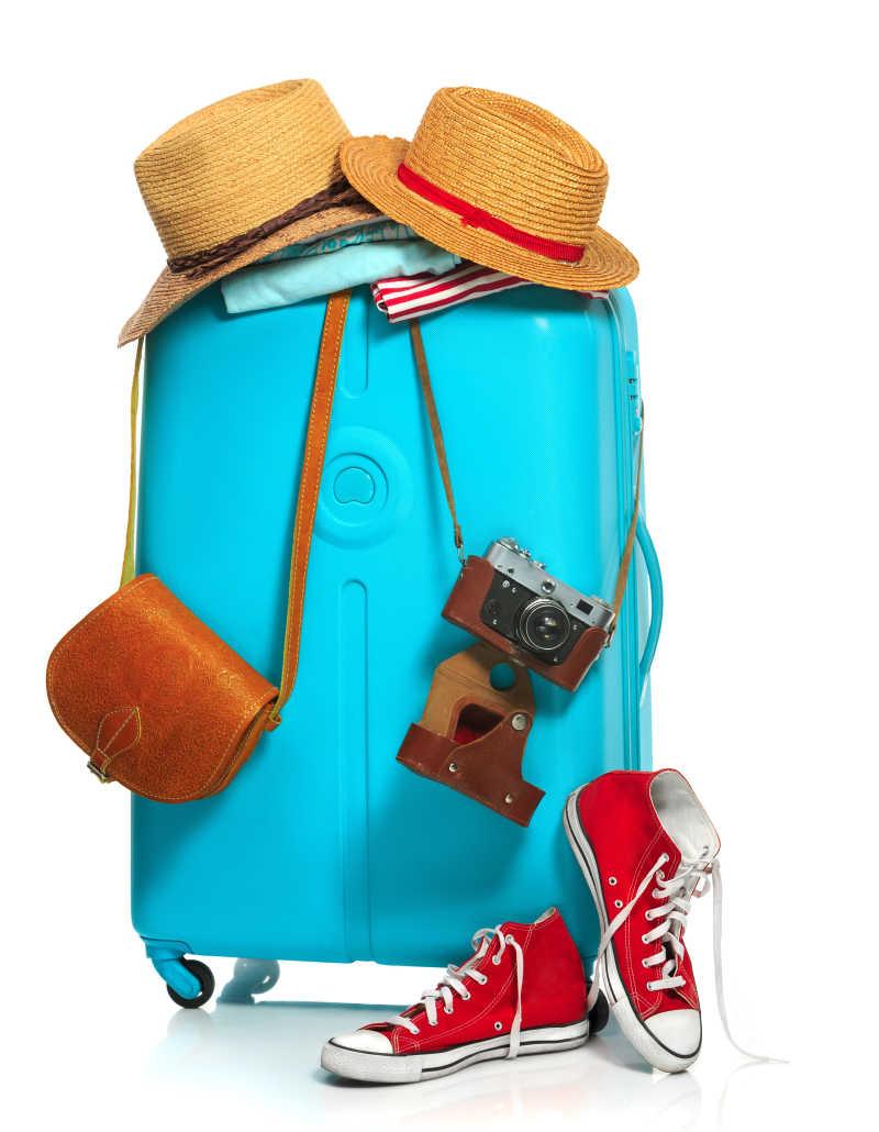 白色背景下挂着背包运动鞋和遮阳帽的蓝色行旅箱