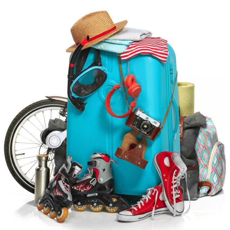 白色背景下放着滑板鞋运动鞋照相机自行车等外出物品的蓝色旅行箱