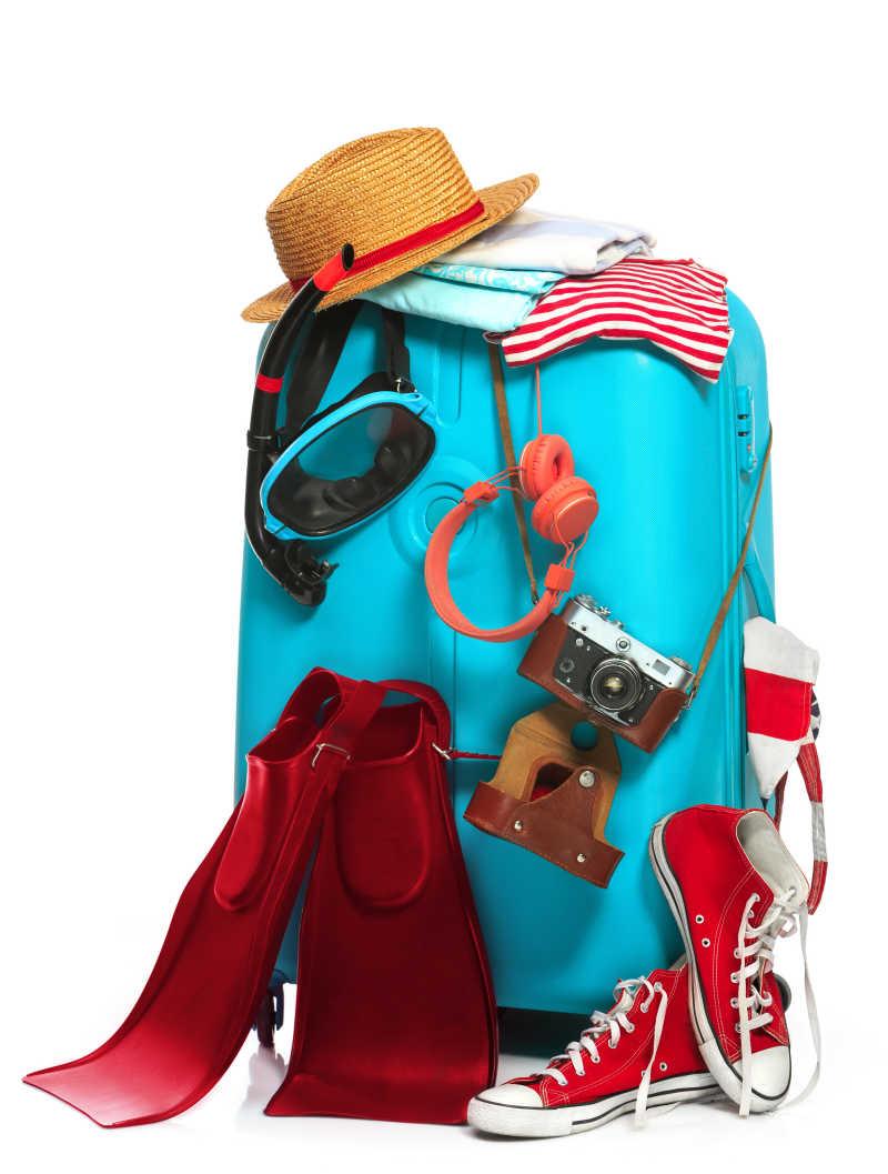 白色背景下挂着相机耳机运动鞋帽子以及游泳鞋的蓝色旅行箱
