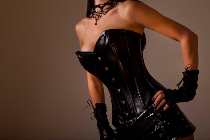 金色背景下穿着黑色皮衣束腰的美女