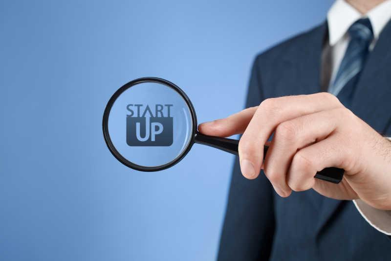 蓝色背景下商人放大镜下的商业启动startup
