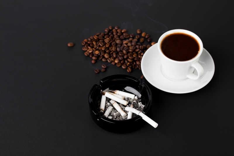 黑色背景下的烟灰缸和咖啡豆