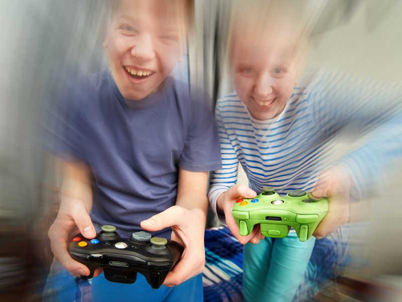 小男孩们一起玩足球游戏机